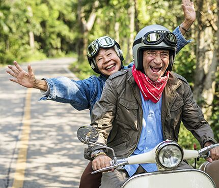 Older couple joyfully riding scooter